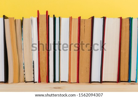 Simple Simple composition of many hardback books, unprocessed books on a wooden table and a yellow background. back to school. Copy space. Education. #1562094307