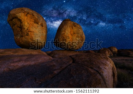 Scenic nocturnal australian outback landscape of Devils Marbles The Eggs by night with milky way, stars field and galaxies. Granite boulders of Karlu Karlu in Northern Territory, Central Australia. Royalty-Free Stock Photo #1562111392