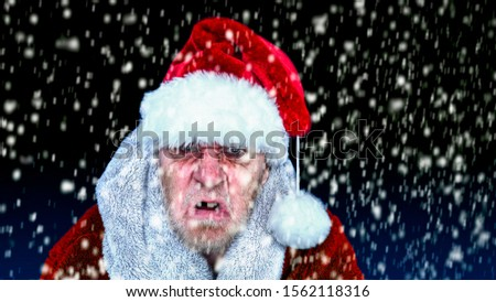 Funny picture of an angry and grumpy horror Santa Claus in a blizzard or snowstorm.