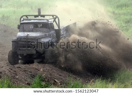 Truck driving fast through the dirt and dust #1562123047