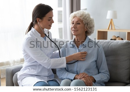 Young woman nurse doctor gp holding stethoscope examining old senior 60s grandma patient check heartbeat at homecare checkup medical visit at home hospital, older people cardiology healthcare concept #1562123131