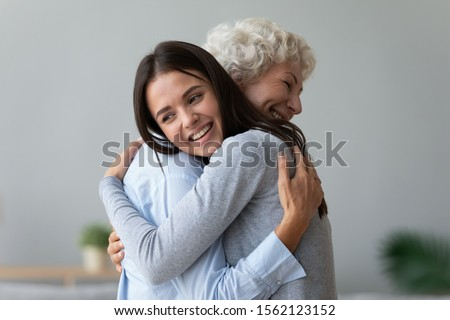 Happy young lady adult daughter granddaughter visiting embracing hugging old senior retired grandmother cuddling bonding, two age generations women expressing love and care at reunion meeting at home #1562123152