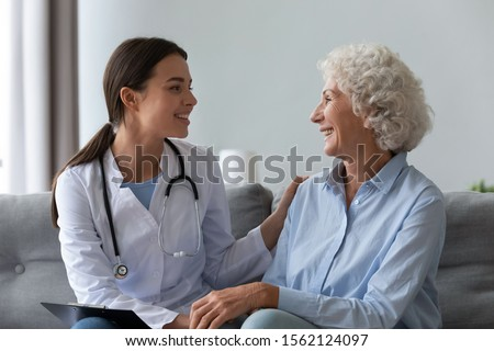 Happy young female nurse provide care medical service help support smiling old grandma at homecare medical visit, lady carer doctor give empathy encourage retired patient sit on sofa at home hospital #1562124097