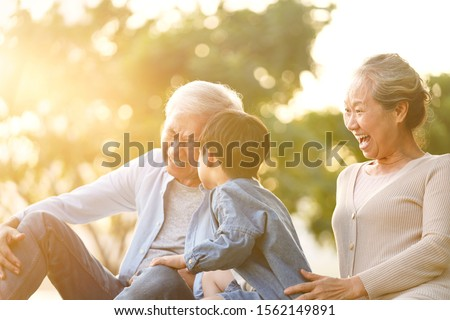 asian grandson, grandfather and grandmother sitting on grass having fun outdoors in park at sunset #1562149891