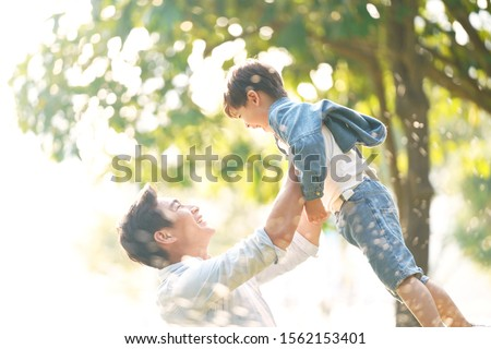 cute little asian boy lifted by father outdoors in park #1562153401