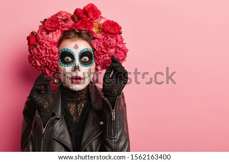 Portrait of emotional woman wears professional sugar skull makeup, has scared face expression, raises hand in black gloves with horror, prepares for Halloween holiday, isolated over pink background #1562163400