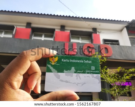 Banyumas, Central Java / Indonesia - October 11, 2019: Asian man hand holding Kartu Indonesia Sehat (Health Insurance card from the Government of Indonesia) under the auspices of the BPJS   #1562167807