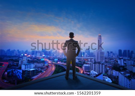 Businessman with black suit standing on top of building of city during sunrise early morning #1562201359