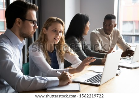 Multiracial younger and older colleagues working in pairs in office. Skilled female employee explaining focused male coworker new software. Confident manager discussing project details with client. #1562219722