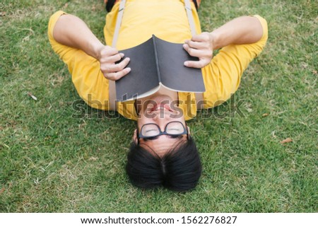 Upside down picture of nerdy guy lie down on the field and reading a book.