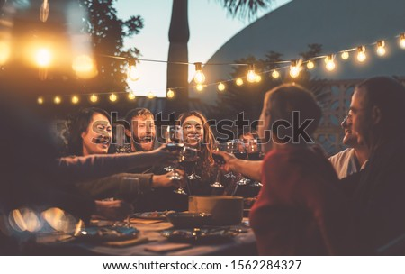 Happy family dining and tasting red wine glasses in barbecue dinner party - People with different ages and ethnicity having fun together - Youth and elderly parents and food weekend activities concept #1562284327
