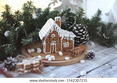 Gingerbread house with christmas decor on wooden background with cones with cinnamon sticks and marshmallows #1562307235