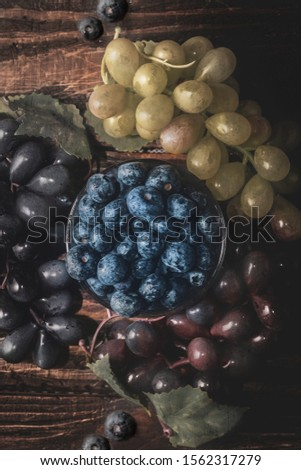 blueberries grapes fruit from above on wood backdrop old style faded desecrated texture healthy food tasty good tasty snack  green red blue health dieting lifestyle ripe condiments cooking ingredient  #1562317279