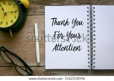 Top view of clock,glasses,pen and notebook written with Thank You For Your Attention on wooden background. Royalty-Free Stock Photo #1562318596