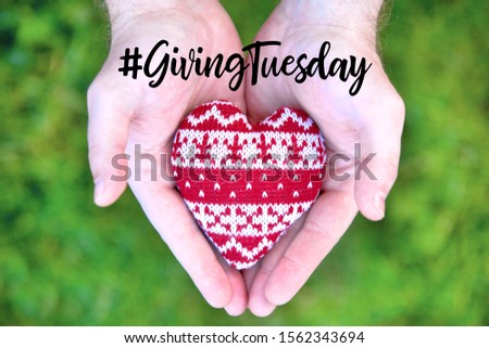 Giving Tuesday is a global day of charitable giving after Black Friday shopping day. Charity, give help, donations and support concept with text message sign and red knitted heart in man handful #1562343694