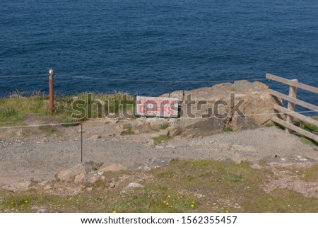 """Dangerous Cliffs"" Sign on a Cliff Top at Lands End on the South West Coast path #1562355457"