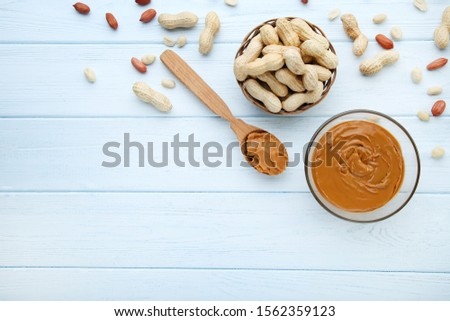 Peanut butter in bowl and nuts on wooden table #1562359123