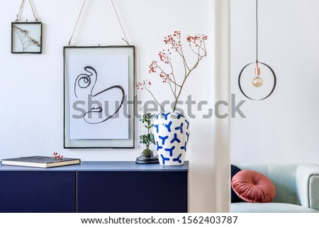 Modern scandinavian interior design of living room with mock up photo frames, navy blue commode, design sofa, flowers in vase and elegant accessories. Stylish home decor.   Template. Ready to use.