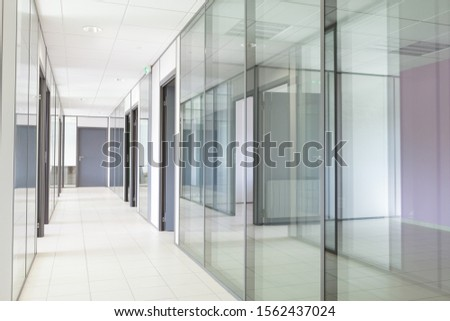 Empty office corridor with transparent walls Royalty-Free Stock Photo #1562437024