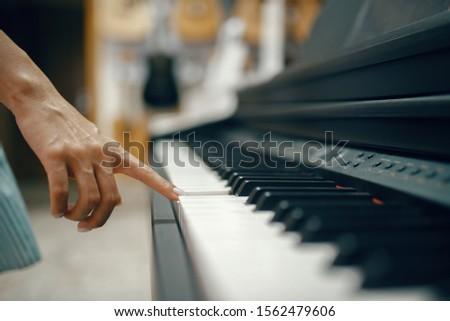 Young woman choosing digital piano in music store #1562479606