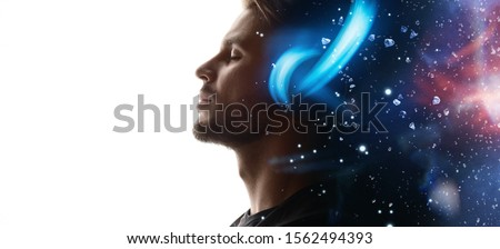 Portrait of man in headphones listening music with closed eyes. Double exposure of male face and galaxy isolated on white background. Digital art. The universe inside us. #1562494393