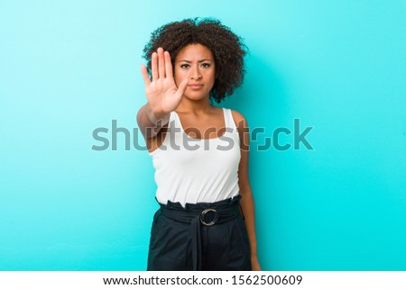 Young african american woman standing with outstretched hand showing stop sign, preventing you.