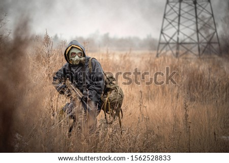 Soldier with rifle in raincoat and gas mask is walking outdoor. #1562528833