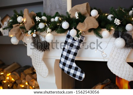 A close picture of beautifully decorated white Christmas socks hanging on fireplace waiting for presents. Christmas socks hanging on fireplace in living room. Christmas decorated fireplace with pine
