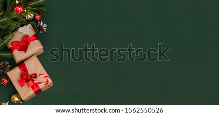 Banner - Christmas and New Year gifts on a green background with copy space with Christmas tree branches and balls. Banner advertising. #1562550526
