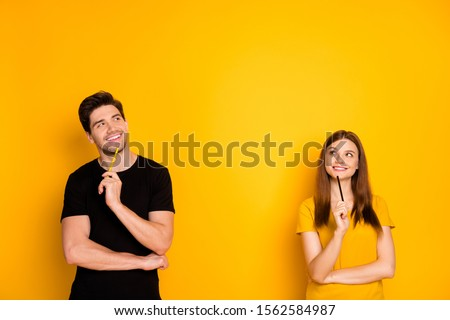 Photo of cheerful positive cute nice charming pretty couple holding pens wearing black t-shirt smiling toothily looking into empty space a fit of thoughts isolated over bright shiny color background #1562584987