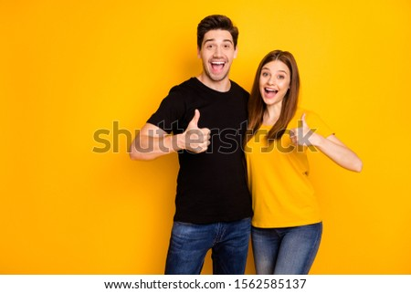 Photo of positive cheerful cute charming girlfriend and boyfriend showing their thumbs up wearing jeans denim black t-shrit expressing kind emotions giving feedback isolated vibrant color background #1562585137
