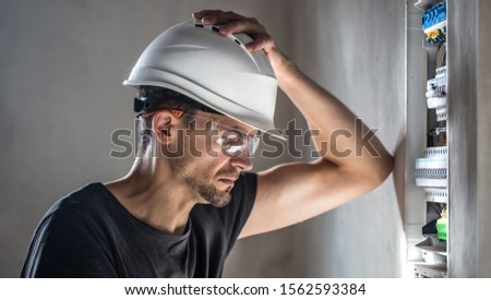 Man, an electrical technician working in a switchboard with fuses. Installation and connection of electrical equipment. Professional with tools in hand. concept of complex work, space for text. #1562593384