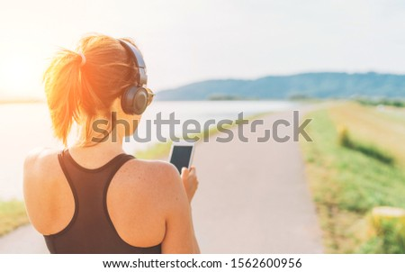Young teenager girl starting jogging and listening to music using smartphone and wireless headphones. Active sport life concept image.