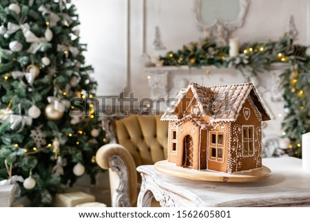 Postcard gingerbread house. Defocused lights of Christmas tree. Holiday mood. Christmas and Happy new year. #1562605801