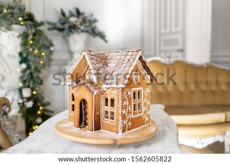 Postcard gingerbread house. Defocused lights of Christmas tree. Holiday mood. Christmas and Happy new year. #1562605822
