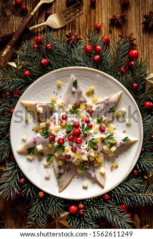 Christmas Herrings fillets with cream sauce with apple, pickled cucumbers, red onion and spices, garnished with cranberries on a ceramic plate on a festive decorated wooden table, top view #1562611249