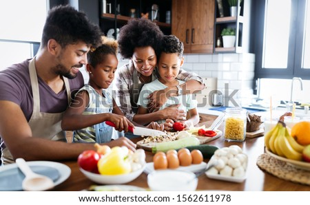 Happy family in the kitchen having fun and cooking together. Healthy food at home. Royalty-Free Stock Photo #1562611978