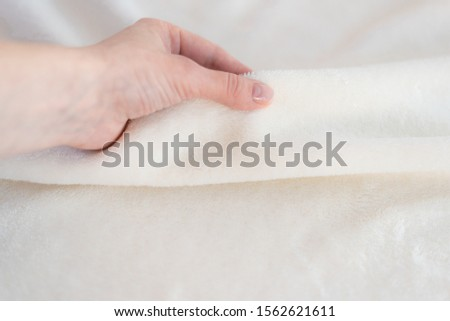 Female hand touches a soft cozy plaid of white fabric with a pile. Textile material, pleasant to the touch #1562621611