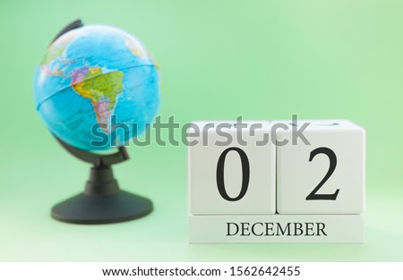 December 2. December month. White cube with numbers and globe on a blurred green background. The concept of New Year and Christmas holidays. #1562642455