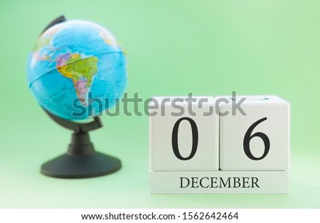 December 6. December month. White cube with numbers and globe on a blurred green background. The concept of New Year and Christmas holidays. #1562642464