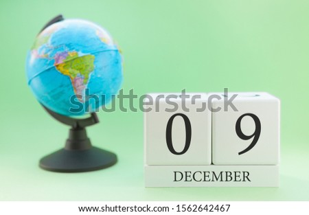 December 9. December month. White cube with numbers and globe on a blurred green background. The concept of New Year and Christmas holidays. #1562642467