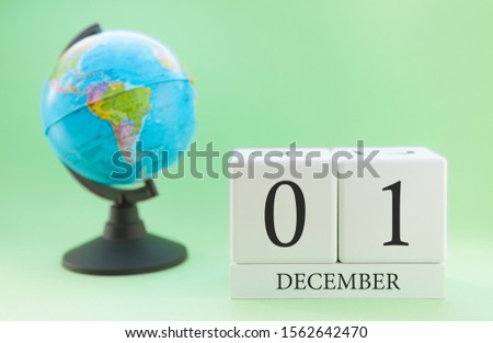 December 1. December month. White cube with numbers and globe on a blurred green background. The concept of New Year and Christmas holidays. #1562642470