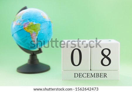 December 8. December month. White cube with numbers and globe on a blurred green background. The concept of New Year and Christmas holidays. #1562642473