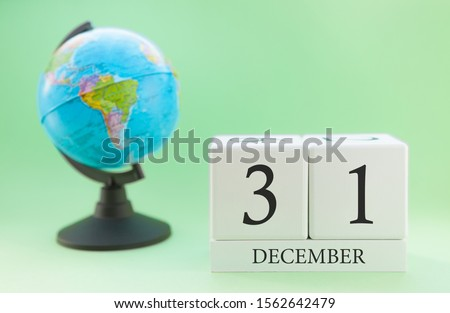 December 31. December month. White cube with numbers and globe on a blurred green background. The concept of New Year and Christmas holidays. #1562642479