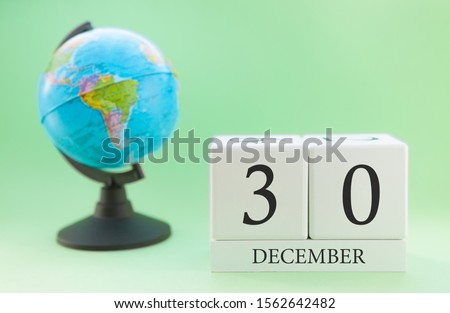 December 30. December month. White cube with numbers and globe on a blurred green background. The concept of New Year and Christmas holidays. #1562642482