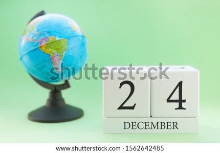 December 24. December month. White cube with numbers and globe on a blurred green background. The concept of New Year and Christmas holidays. #1562642485