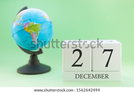 December 27. December month. White cube with numbers and globe on a blurred green background. The concept of New Year and Christmas holidays. #1562642494