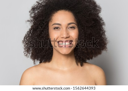 Head shot portrait close up smiling beautiful African American girl with naked shoulders looking at camera isolated on grey background, natural beauty concept, prefect skin, skincare and treatment #1562644393