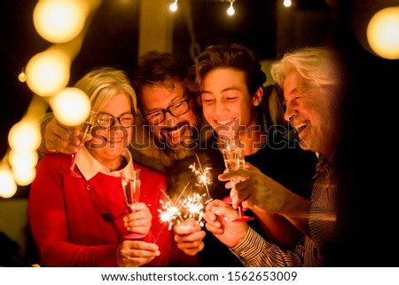 group of two seniors and two adults together having fun with sparlers the new year to celebrate - happy family with lights - holding a glass of champagne #1562653009