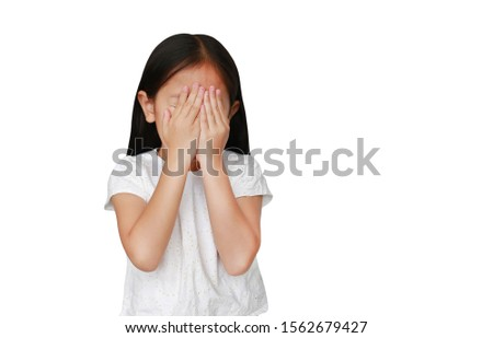 Little caucasian kid girl closing hid eyes by hand isolated on white background with copy space. Kid is crying and rubbing her eyes with her hands. #1562679427